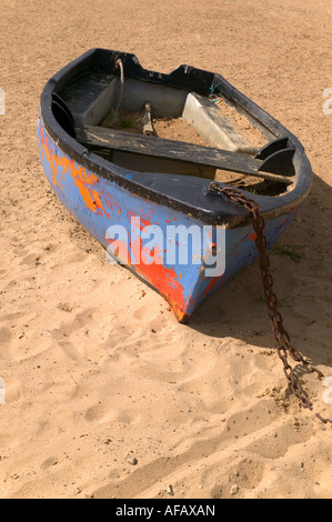 Old boat with peeling paint abandoned on the sand - Stock Photo