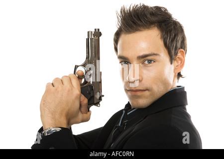 Young man holding hand gun, close-up - Stock Photo