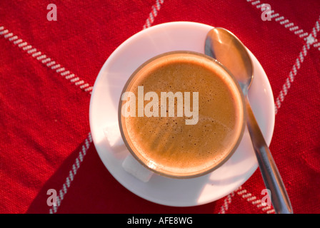 Cafe latte in clear glass cup on red tablecloth - Stock Photo
