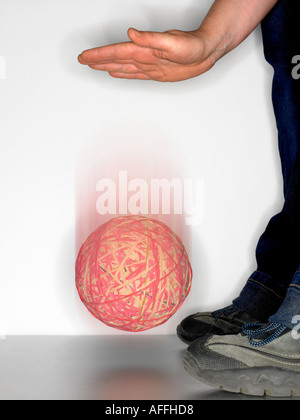 dropping a rubber band ball - Stock Photo