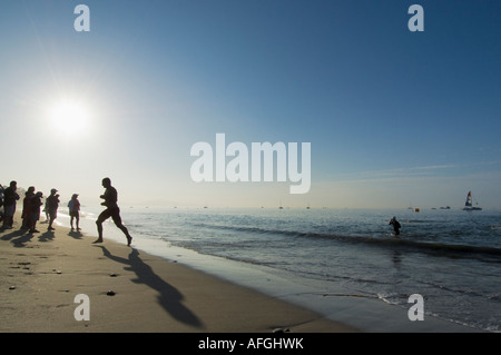Racers exit water and run up beach after ocean swimming section of Santa Barbara Triathlon, California, 2007 - Stock Photo
