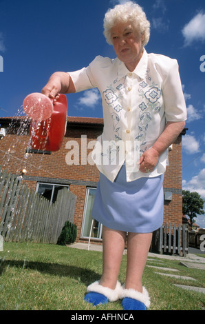 An elderly lady wearing slippers waters her garden with a watering can during water shortage - Stock Photo