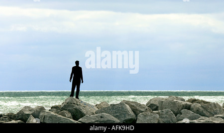 Silhouette of young man standing on rocks at lakefront of Lake Michigan - Stock Photo