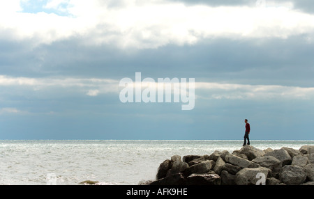 Silhouette of young man standing on rocks at lakefront Milwaukee Wisconsin USA - Stock Photo