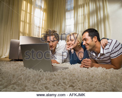 Friends watching something on the laptop. - Stock Photo