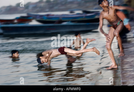 Boys swimming in the Ganges Varanasi India - Stock Photo