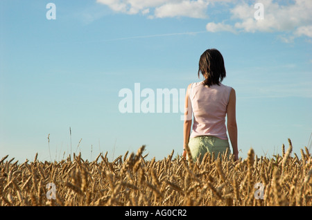 Young woman in wheat field looking into distance - Stock Photo