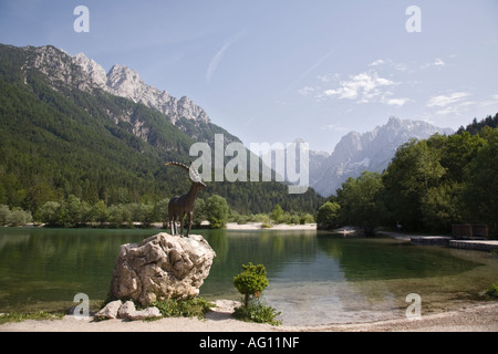 Gold Horn Ibex statue by Jasna lake with mountains in 'Triglav National Park' beyond. Kranjska Gora Slovenia - Stock Photo