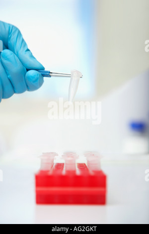 Scientist picking up test tube with tweezers in laboratory, close up of hand - Stock Photo