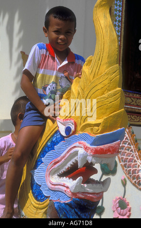 Young boy sitting on a Guardian Dragon outside a Temple or Wat near Phimai Central Thailand  - Stock Photo