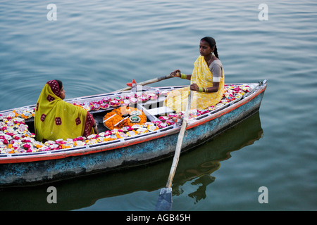 Two woman in a boat on the Ganges River selling deepak or oil lamps Ganges River  Varanasi india - Stock Photo