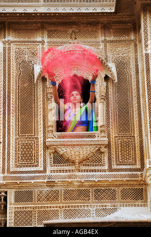 Woman throwing brightly coloured holi powder through a window of a haveli - Stock Photo