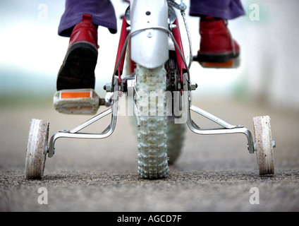 Young child on a bicycle with stabilizers or stabilisers or training wheels - Stock Photo