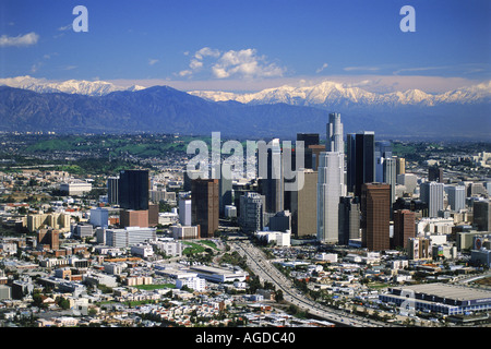 Aerial view of downtown Los Angeles with snow on San Gabriel Mountains - Stock Photo