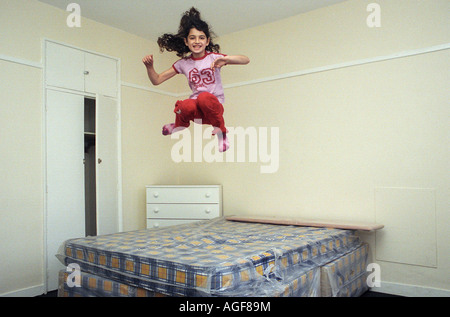 A young girl, aged 9, jumps on a bed in a empty bedroom. - Stockfoto