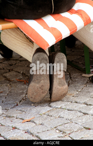man sitting on a bench feet and shoes crosslegged Bavaria Germany - Stock Photo