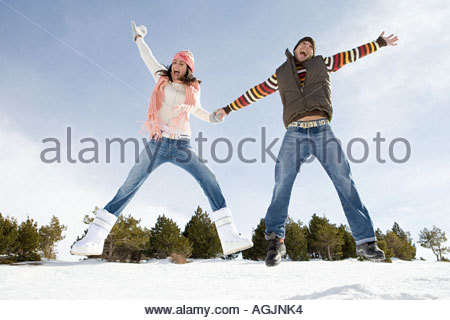 Couple jumping in snow - Stockfoto