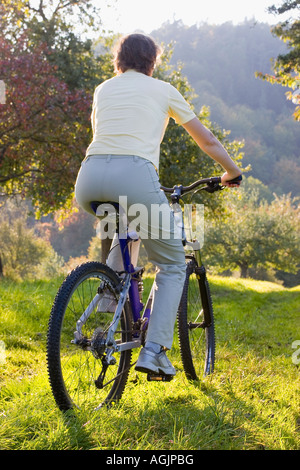 Woman on a mountainbike at sunset in autumn - Stock Photo