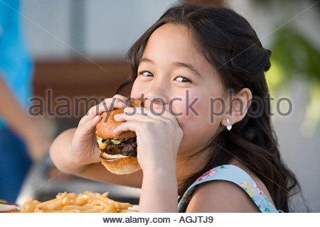Girl eating a burger - Stock Photo