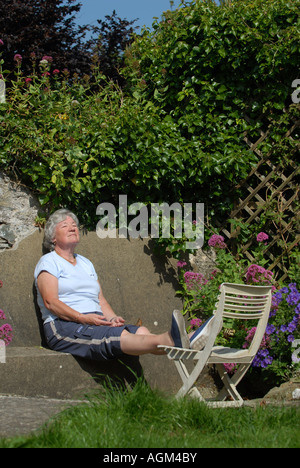 AN ELDERLY PENSIONER WOMAN ENJOYS SUNBATHING IN HER WALLED GARDEN.UK - Stockfoto