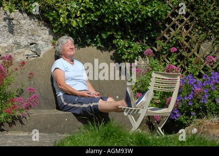 A OLD AGE PENSIONER  WOMAN ENJOYS SUNBATHING IN HER BACK GARDEN RE RETIREMENT AUTUMN YEARS.UK - Stockfoto