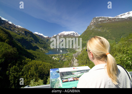Woman absorbing the panoramic view of the Geirangerfjord from a hillside viewpoint Geiranger Norway - Stock Photo