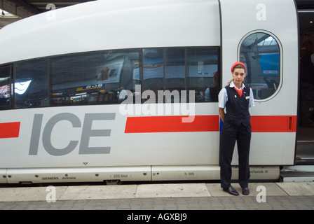 Attendant stands beside German Intercity ICE high speed trains at  in Munich station Bavaria Germany - Stock Photo
