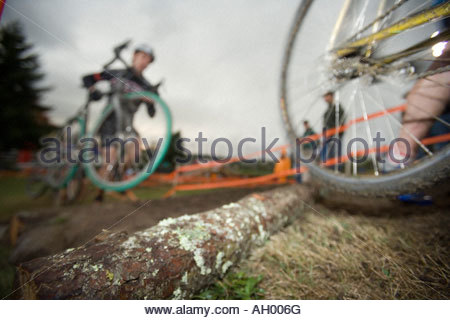 Athlete carrying bicycle during race - Stock Photo