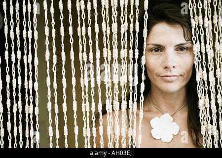 Close-up of a mid adult woman peeking through a beaded curtain - Stock Photo