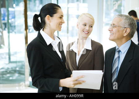 Business associates standing, smiling at each other, one holding binder - Stock Photo