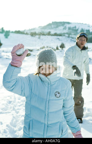 Brother and sister throwing snowballs, girl's eyes closed - Stock Photo