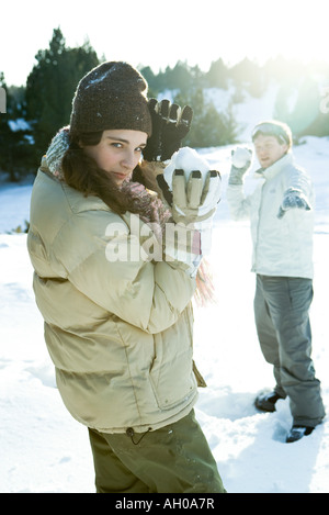 Two young friends holding up snowballs, one looking over shoulder at camera - Stock Photo