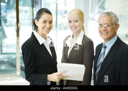 Business associates smiling at camera, one woman holding stack of documents - Stock Photo