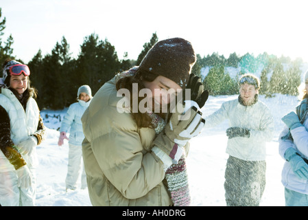 Young friends throwing snowballs, smiling, blurred motion - Stock Photo