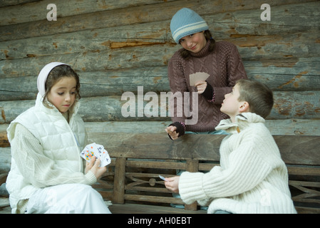 Young friends playing cards outdoors, dressed in winter clothing - Stockfoto