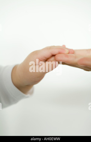 Baby holding adult's fingers, cropped view - Stockfoto