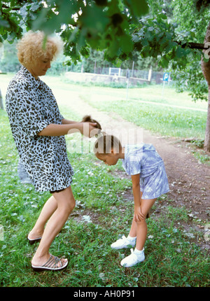 doing hairstyle in park mother and daughter - Stock Photo