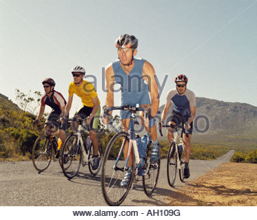 Four bikers on a country road - Stock Photo