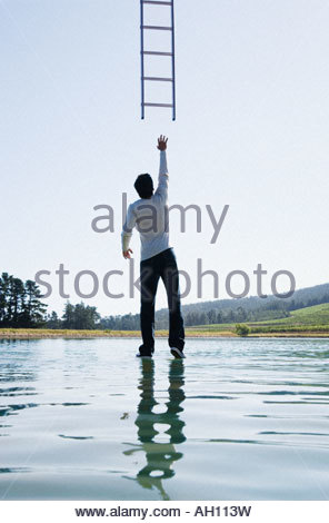 Man standing on water reaching for ladder rear view - Stock Photo
