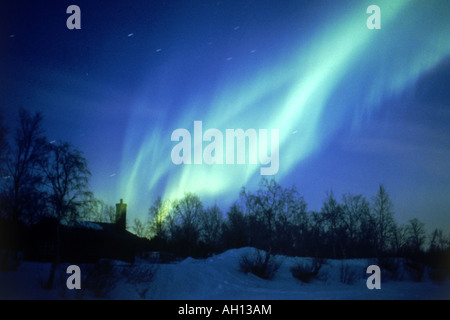 Aurora borealis or northern lights moving across night sky above Arctic Circle in Sweden - Stock Photo