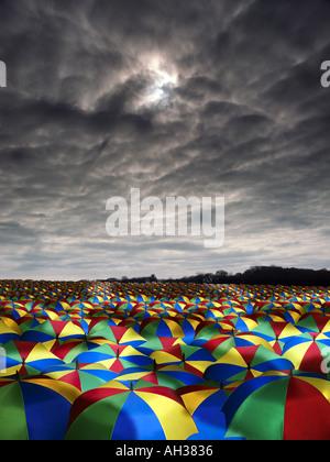 vast sea of coloured colored umbrellas with dark sky overhead rain - Stock Photo