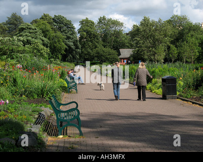 People walking a dog in Kelvingrove Park, Glasgow. - Stock Photo