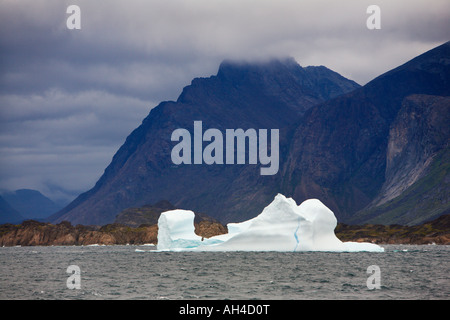 Dramatic mountains under heavy low grey sky with white iceberg in contrast floating on sea off the southwest coast - Stock Photo