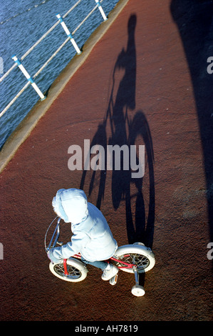 A child on a bicycle fitted with stabilisers casting a shadow - Stock Photo