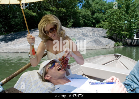 Young woman sitting in a boat feeding grapes to a young man resting on her lap - Stockfoto