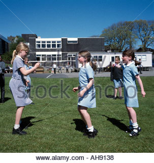Schoolgirls skipping in playground of primary school Isle of Man UK - Stockfoto