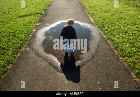 small boy looking down at puddle and shadow along a walkway - Stock Photo