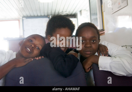 Three uniformed South African school children on the ferry to school on Robben Island - Stock Photo