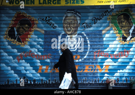 125th Street Harlem, a black lady walks past mural featuring Malcolm X Bill Clinton and Martin Luther King. NYC, - Stock Photo
