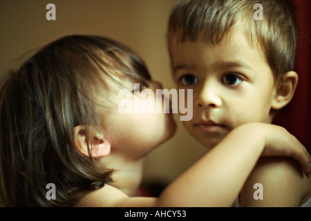 A sister kisses her brother with her hand on his shoulder as they hold each other early in the morning - Stock Photo
